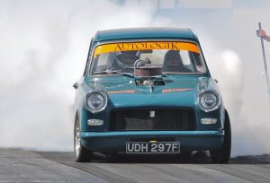 Picture of a Herald drag race car owned by Tony North performing a burn out.